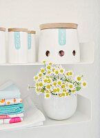 Labelled, china spice jars with wooden lids, posy of chamomile and tea towels with neon prints on metal shelves