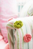 Green and pink crocheted roses on blanket