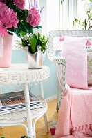 Vase of flowers on white wicker side table next to matching armchair with pink patterned cushions