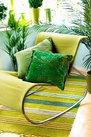 Modern rocking chair with green cover and scatter cushions in shades of green on striped rug