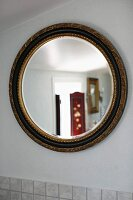 Round mirror with gilt frame on white wall