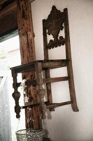 Antique, carved kitchen chair hung on wall