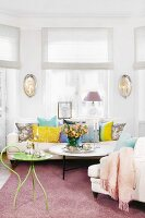 Delicate, green metal side table and coffee table in front of comfortable sofa with scatter cushions in window bay