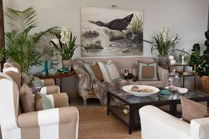 Living room with sand-coloured upholstered seating, house plants and picture of aquatic bird