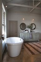 Free-standing bathtub below window and long washstand with base cabinet in spacious bathroom with rustic ambiance