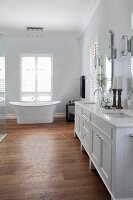 White, country-house-style washstand with twin sinks and free-standing bathtub in front of French windows