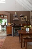 Rustic dining area with old wooden table in open-plan kitchen