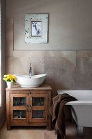 Antique, Indian cabinet used as washstand next to modern, free-standing bathtub and framed picture of animal on wall