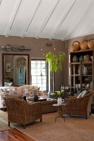 Wicker chairs and sofa on sisal rug in living room decorated in warm, earthy shades