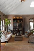 Wicker armchair and sofa on sisal rug in front of glass-fronted cabinet in living room in warm earthy shades