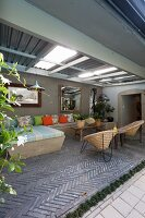 Masonry benches with many cushions and wicker easy chairs on roofed terrace with herringbone brick floor