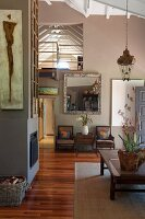Simple, open-plan, Colonial-style interior with mezzanine; African artwork on side of chimney breast in foreground