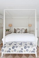 Double bed with white four-poster frame and bench with floral white and blue upholstery at foot