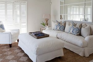White ottoman and matching sofa with arranged scatter cushions in elegant interior with maritime ambiance