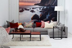Set of coffee tables and grey sofa in front of mural wallpaper showing sunset on rocky coast