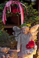 Stone angel lit from one side in front of ivy wreath in garden