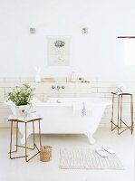 Free-standing vintage bathtub and delicate metal side tables in front of walls with white subway tiles