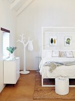 Double bed with white frame and clothes stand in shape of stylised tree in bright attic bedroom
