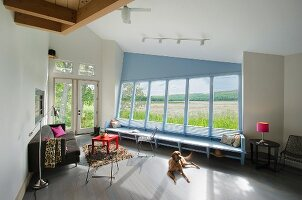 Pet dog relaxing in living room with view of field through bay window at Burlington; Vermont; USA