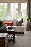 Wohnzimmer mit weisser Couch und Couchtisch vor Fenster mit Gartenblick