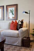 Floor lamp by cropped couch in the living room; California; USA