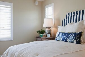 Arranged pillows on bed with lit table lamp in bedroom; California; USA