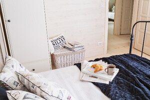 Dark metal bed with breakfast tray on dark blanket in wood-panelled room