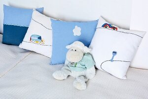 Soft toy sheep leaning against nursery cushions on white blanket