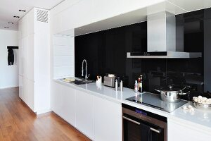 Cool, white fitted kitchen with black glass splashback