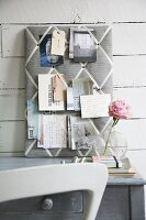 Fabric-covered pin board with grid of diagonal ribbons above grey shabby chic desk and white chair