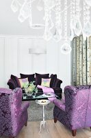 Purple upholstered furniture with the crystals on a chandelier in thr foreground