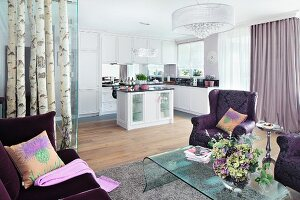 A view from a seating area with purple upholstered furniture and an acrylic table looking towards a white, fitted kitchen with an island counter