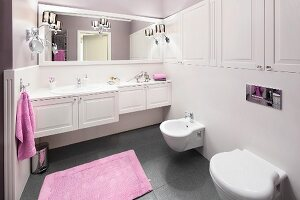 Lilac towels giving a touch of colour to an elegant bathroom with white, built-in cupboards and a grey floor