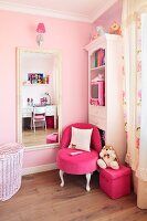 White antique style furniture and a neon pink upholstered chair against a pale pink painted wall in a little girl's bedroom