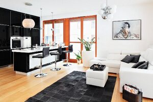 An open plan living area with a view towards a breakfast bar and a sitting area in black and white