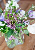 Bouquet of white & purple garden flowers in glass vase