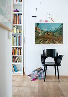 Black-painted retro armchair below landscape painting on wall
