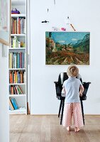 Young child in front of black armchair below landscape painting on wall