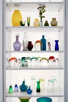 Glasses and vases of various colours and styles on modern shelves