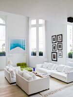 White sofa set in living room with French windows leading to balcony in period apartment