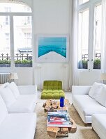 White sofa set, rustic wooden coffee table and green futon chair between standard lamps in white living room