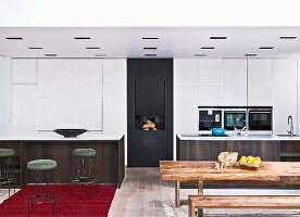 Rustic wooden table and bench in front of open-plan kitchen, delicate, retro-style bar stools at monolithic counter in front of white fitted cupboards