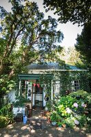Vintage cottage in mature garden with flowering bush and colourful bunting on porch