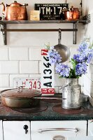 Wall-mounted shelf above nostalgic cooker and copper pans in Swedish vintage kitchen