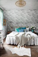 Comfortable, country-house bedroom with wallpapered sloping ceiling, wooden floor and romantic double bed with white bedlinen