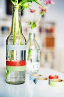 Single flowers in glass bottles decorated with washi tape