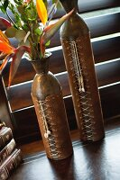Close-up of two ornate brown vases on table