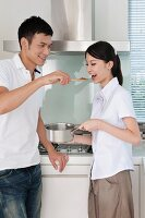 Man feeding woman with a spoon in the kitchen
