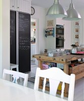 View across dining table to rustic kitchen counter in front of fitted fridge with chalkboard doors