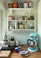 Retro kitchen appliance and espresso machine on worksurface below shelves of storage jars